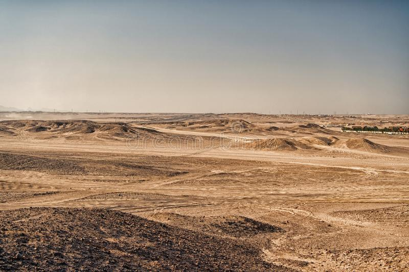 Desert landscape on clear blue sky background. Dune land with dry terrain surface. Ecology and global warming effect. Hopelessness and lifeless concept, copy stock photo