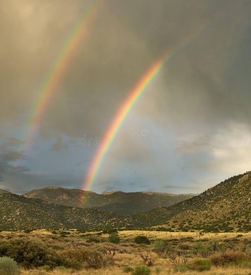Desert Landscape: Double Rainbow over Mountains. A double rainbow appears over Albuquerque's Sandia Mountains during the monsoon season stock photo