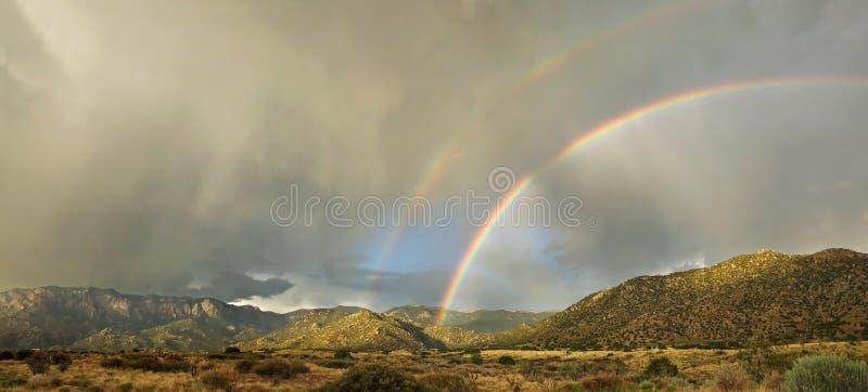 Desert Landscape: Double Rainbow over Mountains. A rare double rainbow appears over Albuquerque's Sandia Mountains in the monsoon season stock photos