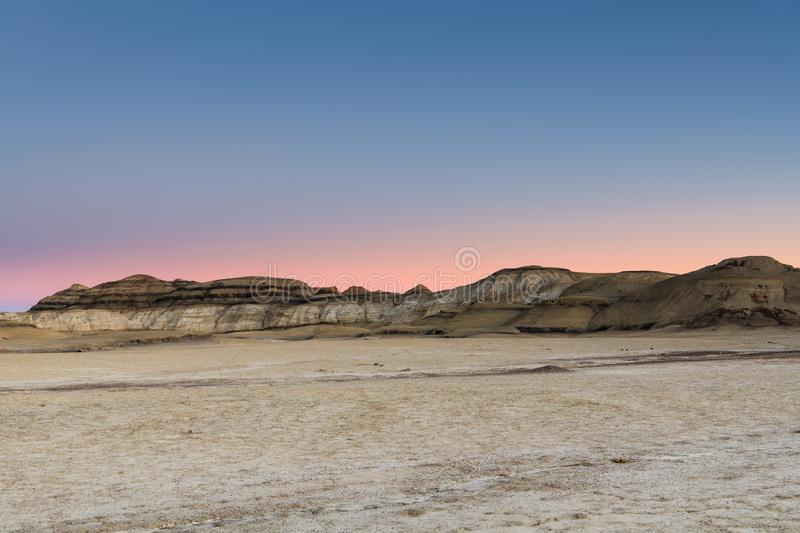 The glowing sky of sunset over the desert landscape of the Bisti Badlands of New Mexico royalty free stock photo