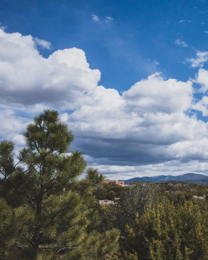 Desert landscape near Santa Fe, New Mexico, USA. Desert landscape with trees under blue sky and clouds, in Museum Hill, Santa Fe, New Mexico, USA stock photography