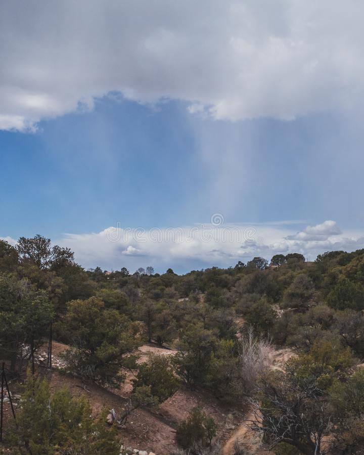 Desert landscape near Santa Fe, New Mexico, USA. Desert landscape with trees under blue sky and clouds, in Museum Hill, Santa Fe, New Mexico, USA royalty free stock image