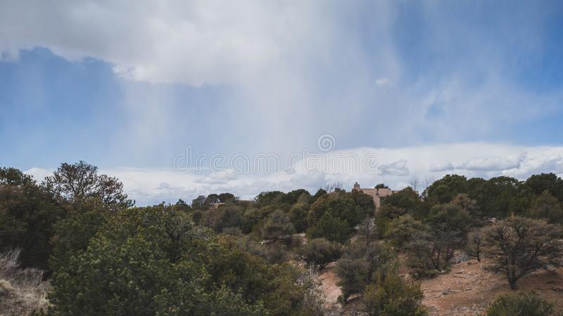 Desert landscape near Santa Fe, New Mexico, USA. Desert landscape with trees under blue sky and clouds, in Museum Hill, Santa Fe, New Mexico, USA royalty free stock photography