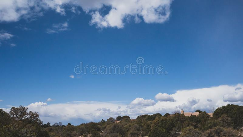 Desert landscape near Santa Fe, New Mexico, USA. Desert landscape with trees under blue sky and clouds, in Museum Hill, Santa Fe, New Mexico, USA royalty free stock images