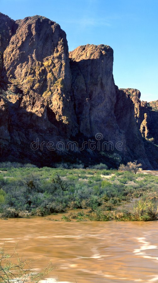 Desert Mountain Flood. Colorful desert mountain during late afternoon sun by a flooding river royalty free stock image