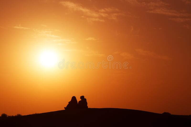 Desert nomads on the crest of a barchan at sunset. Living in the Sands stock photography