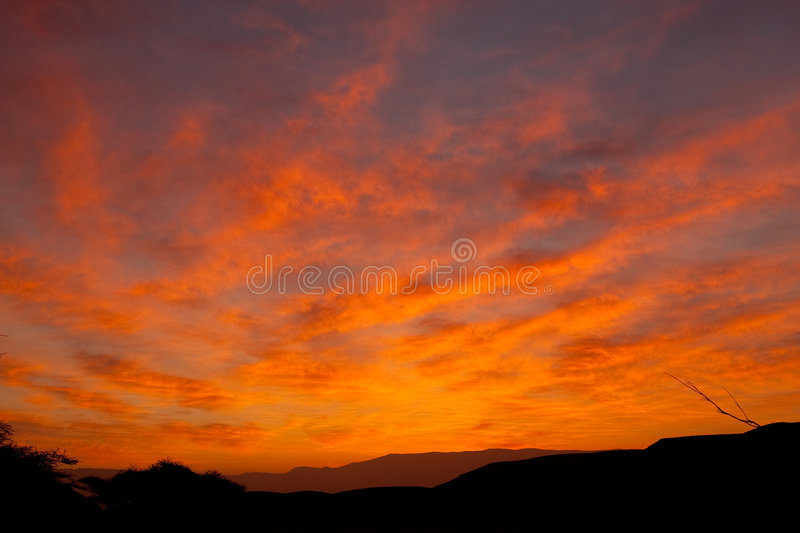 Desert red sky with clouds. Desert sky at sunrise with red clouds stock photo