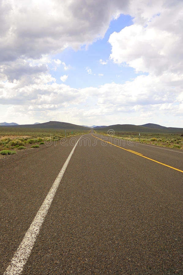 Desert Road. A near-the-ground shot of a long and flat road through the desert with sagebrush, hills and sky royalty free stock photography