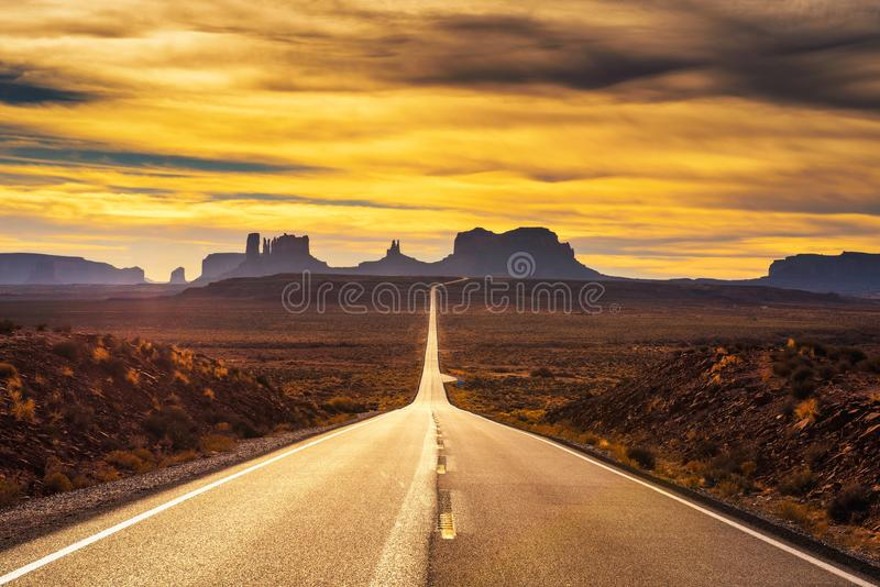 Desert road leading to Monument Valley at sunset stock photos