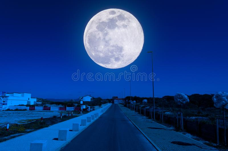 Desert road near the beach at night. With super moon, blue, sky, landscape, sea, nature, full, light, background, moonlight, dark, water, lunar, ocean, black stock photos