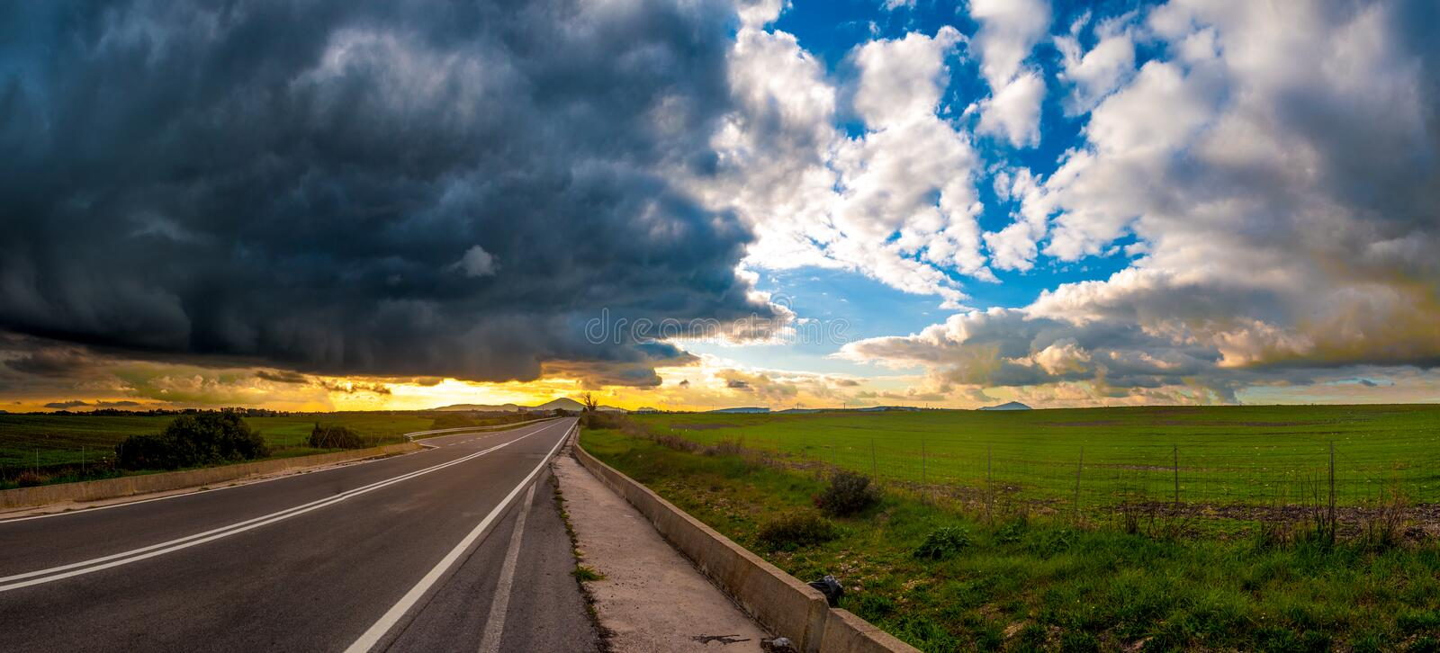 Desert road under a dramatic sky royalty free stock photography