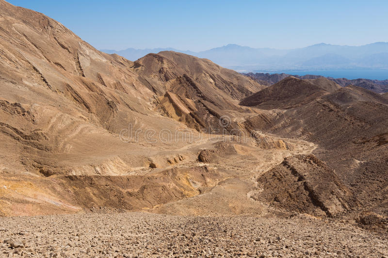 Desert rocks mountains and Eilat Red sea bay. Stone desert mountains cliffs near Eilat Red sea bay, dry riverbeds canyons gorges, Negev desert, Israel royalty free stock image