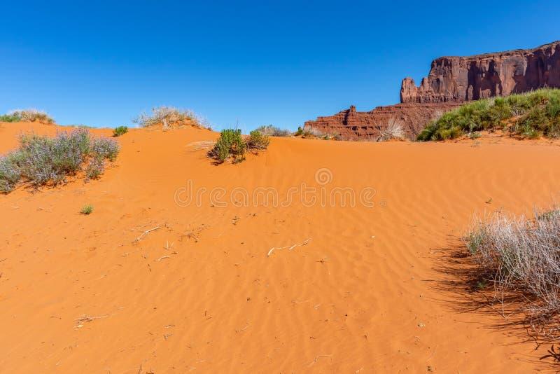 Desert sand dune. Monument Valley Tribal Park, USA. Red sand dune, Monument Valley desert, Navajo Tribal Park, USA. Rocks and sand against blue sky background royalty free stock photo