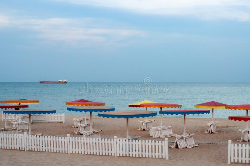 Desert seascape with white deck chairs under colorful beach umbrellas royalty free stock image