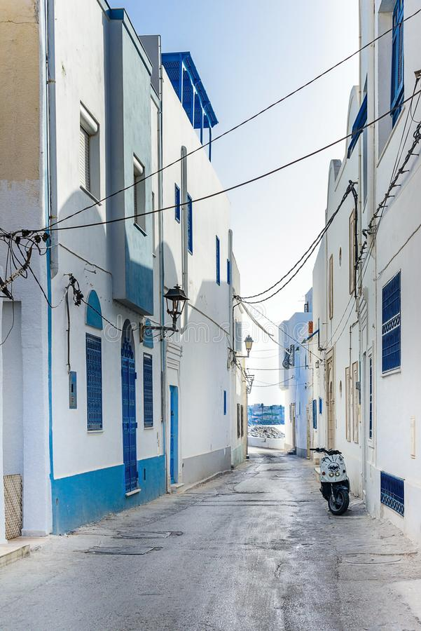 Desert Street in North Africa, Mahdia, Tunisia. White buildings, blue balconies and doors, on the right is a moped, sunny noon stock photos