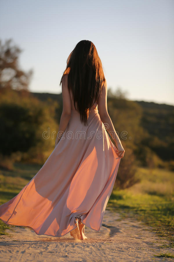 Desert stroll. Young model wearing a floor long dress walking on a desert path during sunset stock photography