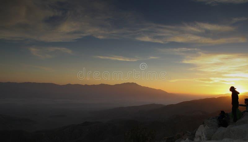 Desert sunset blocked by lone hiker. Dark desert sky sunset with sun shadowed by lone hiker on hilltop royalty free stock images