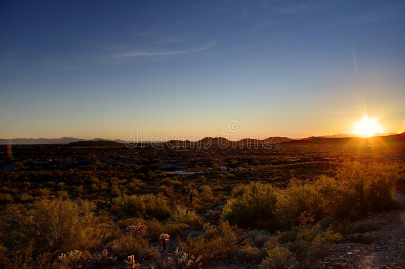 Desert Sunset. Phoenix, Arizona - The sun setting in the desert over mountains in the distance royalty free stock photos