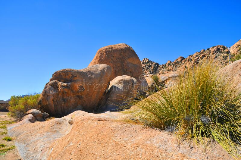 Desert Terrain Mountain Rocks against a bright Blue Cloudless Sky. HTB website design background by Katharina Notarianni royalty free stock photo