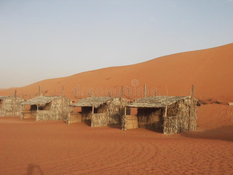 Desert view and Desert Barasti Huts, Wahbia Sands, Oman royalty free stock photo