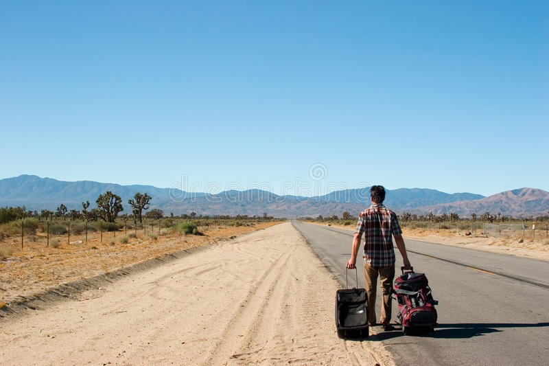 Desert Walk. A man walking and dragging his luggage on the road stock image