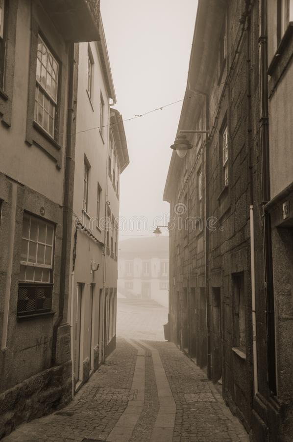 Old houses and deserted alley in the morning mist stock photos