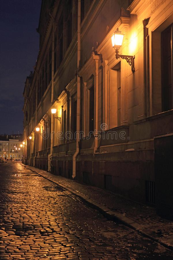 Deserted ancient evening city street with paving stones. Deserted old evening city street with a cobblestone road royalty free stock photo