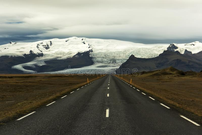 Deserted asphalt straight road on the background of glacial mountains. Landscapes of Iceland. The spirit of adventure and travel. stock images