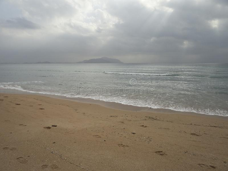 Deserted beach and endless sea in cloudy weather royalty free stock image