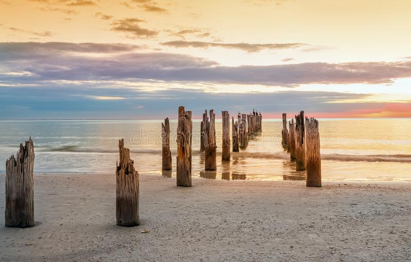 Deserted beach and and the remains of the ruined pier in the water stock photos