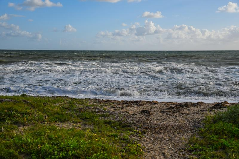 Deserted Beach with Rolling Waves. A deserted beach background scene with sand dunes and rolling, breaking waves in the foreground and a cloudy sky on the royalty free stock photos