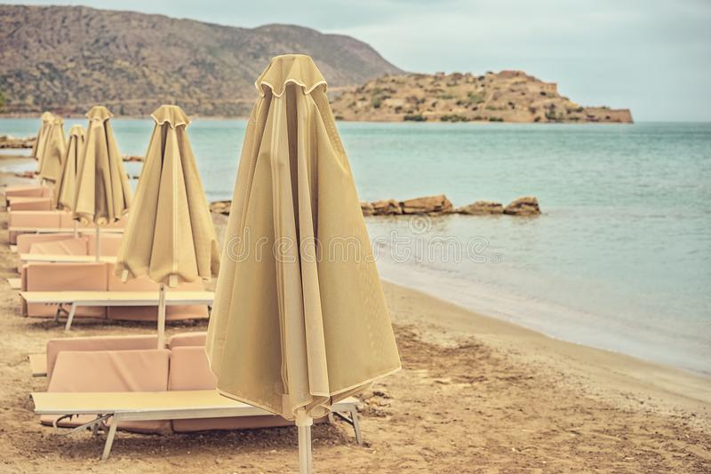 Deserted beach with sun umbrellas and sun beds. On a cloudy summer day. Greece, island Crete. Photo toned royalty free stock photography