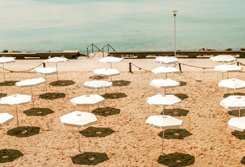 Deserted beach with white umbrellas. Image of a deserted beach in a sunny day royalty free stock photos
