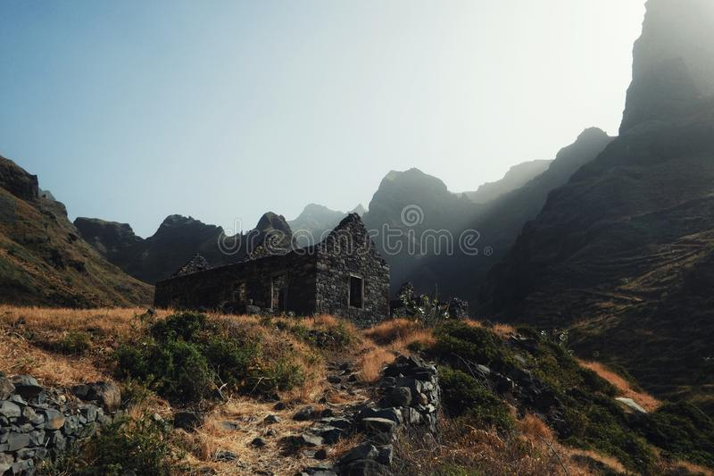 deserted building in the middle of one of the valleys at sunset with yellow grass, high cliffs and god rays peaking thru the rocks royalty free stock images