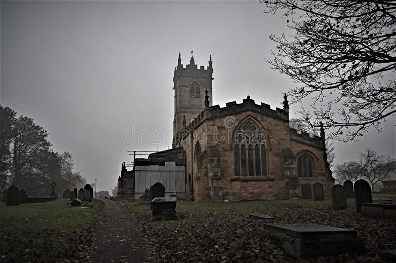 Deserted church and Gothic graveyard, in the bleakness of winter. Capturing a truelly Gothic look to the church in Barnburgh, Doncaster, South Yorkshire on a royalty free stock photography