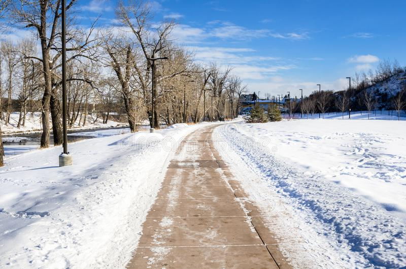 Deserted Cleared Path through a Park Covered in Snow. Deserted Path Cleared of Snow in a Park on a Winter Day. Calgary, AB, Canada stock images