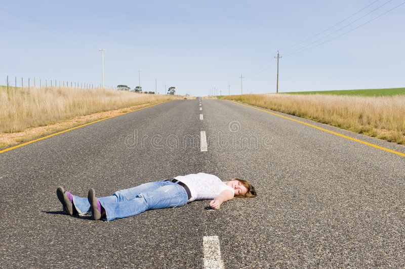 Deserted country-road with girl lying in the middl royalty free stock image