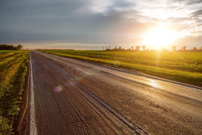 Deserted danificou a estrada asfaltada que estica na distância contra o contexto de nuvens de trovão e do sol de ajuste fotografia de stock