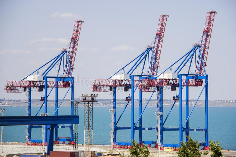 Deserted port terminal in a harbour for loading and offloading cargo ships and freight with rows of large industrial cranes to lif stock images