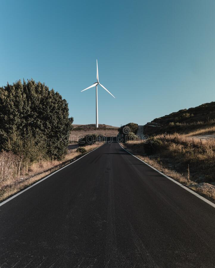 Deserted road with windmill in the background royalty free stock image