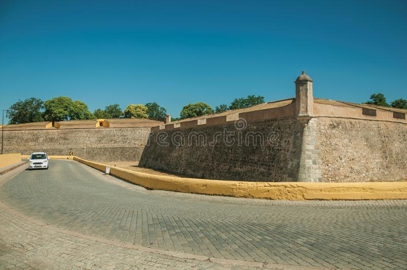 Deserted street with car next to the city wall corner. With watchtower and dry moat, in a sunny day at Elvas. A gracious star-shaped fortress city on the royalty free stock photo