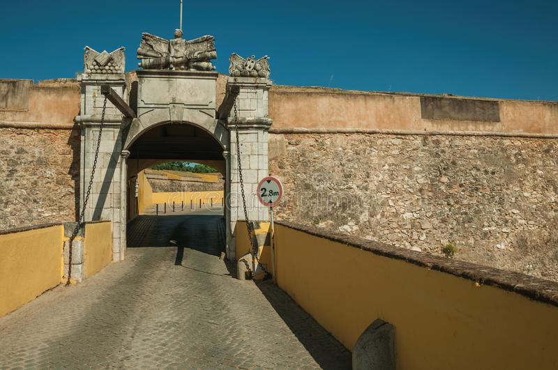 Deserted street going toward city wall gateway. Deserted street going toward the richly decorated city wall gateway and traffic sign, in a sunny day at Elvas. A royalty free stock photo
