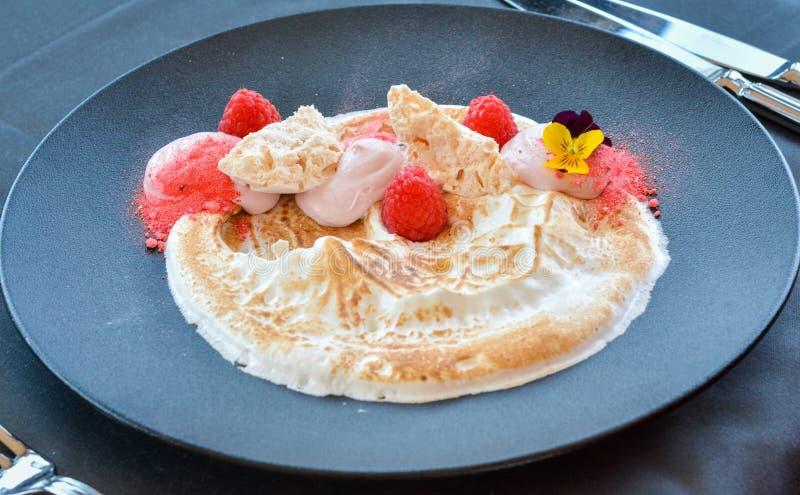 Deserto crema bianco con i lamponi sulla banda nera in ristorante immagine stock