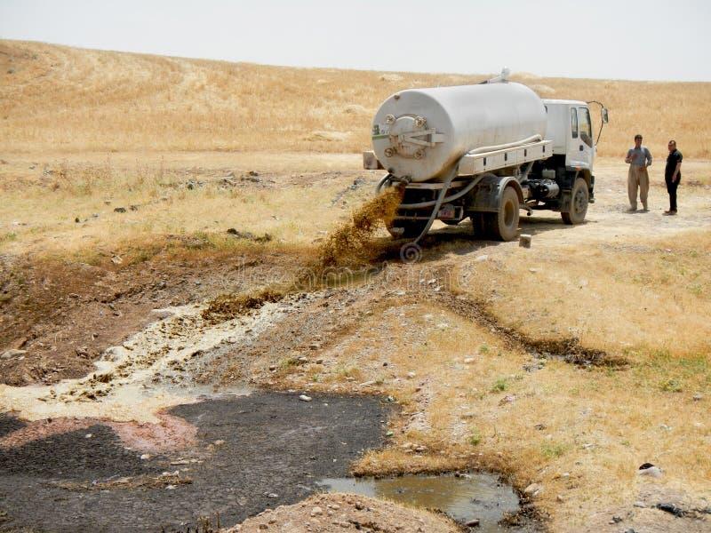 21 05 2017, deserto fora do acampamento de Kawergosk, Iraque : Um caminhão da água de esgoto está despejando sua carga fora do ca fotos de stock royalty free
