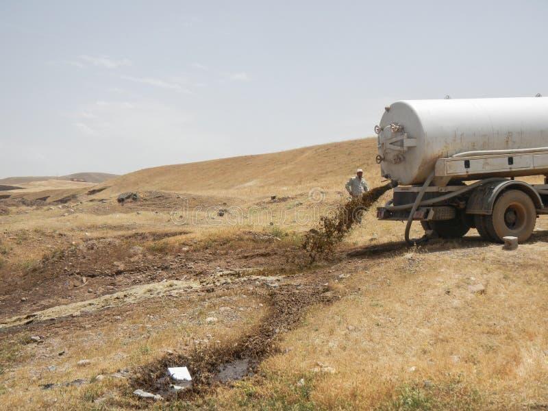 21 05 2017, deserto fora do acampamento de Kawergosk, Iraque : Um caminhão da água de esgoto está despejando sua carga fora do ca foto de stock royalty free