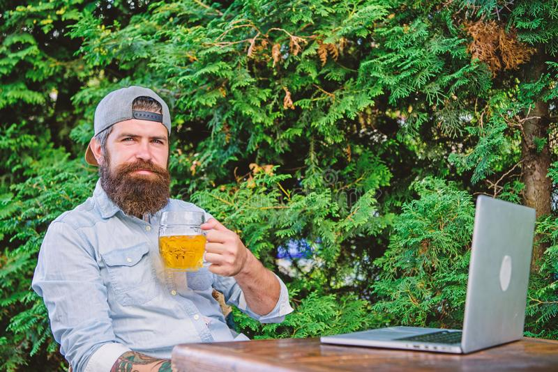 He deserve this pint. Brutal man leisure with beer and online game. Finally friday. Hipster relax sit terrace outdoors stock images