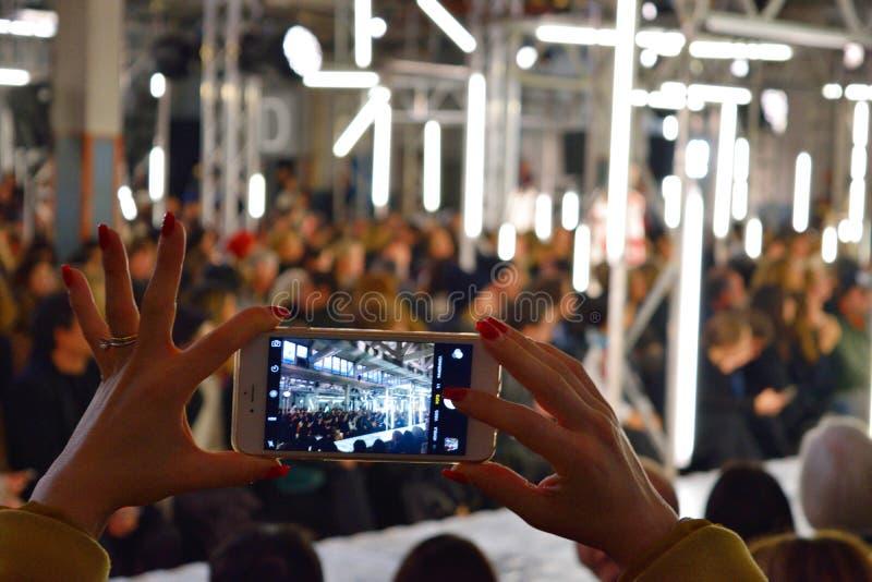 Desfile de moda del tiroteo de la mujer con el teléfono móvil foto de archivo libre de regalías