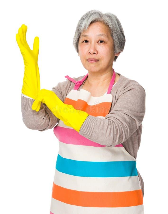 Desgaste da senhora idosa de luvas plásticas para a proteção fotografia de stock royalty free