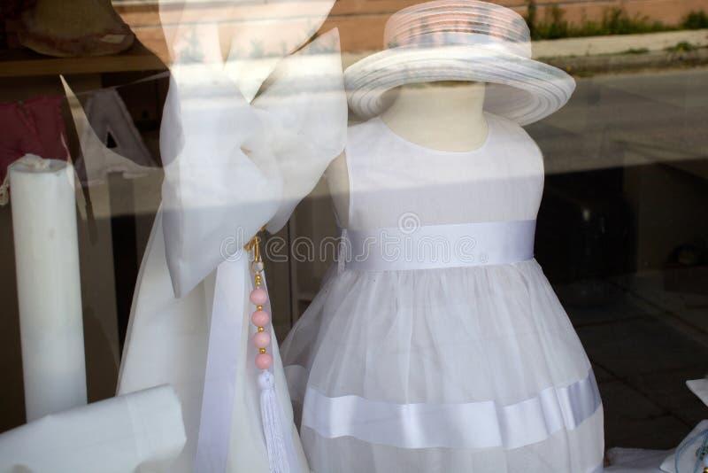 Desgaste formal y accesorios para los niños en ocasiones especiales Vestido y Straw Hat de cóctel en ventana de exhibición Tulle  fotografía de archivo libre de regalías