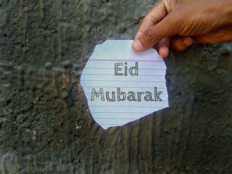 Desideri di Eid Mubarak scritti su pezzo di carta che tiene a disposizione immagini stock libere da diritti